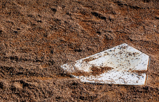 close up shot of a homeplate in a mound of dirt