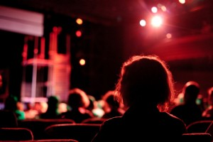 blurry image of heads facing a theatre stage