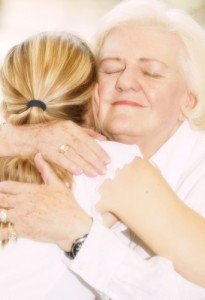 granmotherly woman hugging young child with ponytail