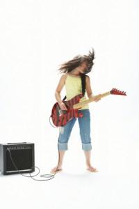 teenage girl playing eletric guitar with amp