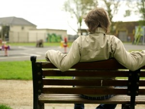 teenage boy on bench with his back facing us