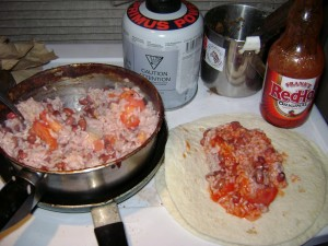 rice in a pan with burrito next to it