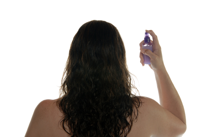 Woman spraying hair with styling product..