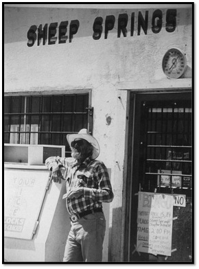 older man in cowboy hat in front of sheep springs trading post