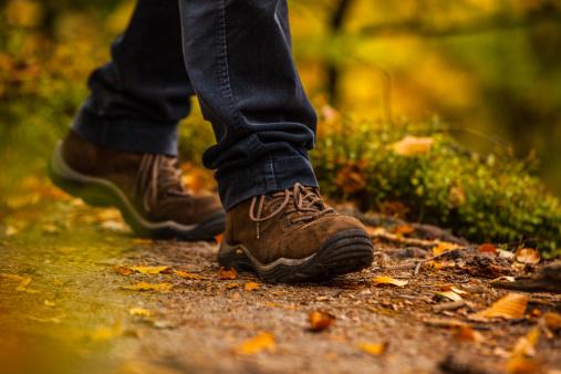 Close up of legs walking in narrow walkway in woods