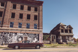 blighted business and home in detroit with old car in front