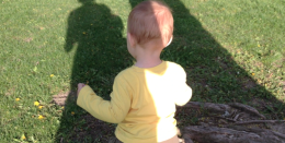 baby in grass with shadow