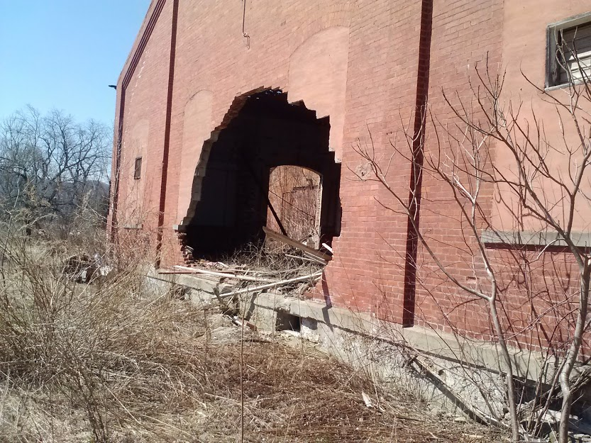 hole in brick wall in large building