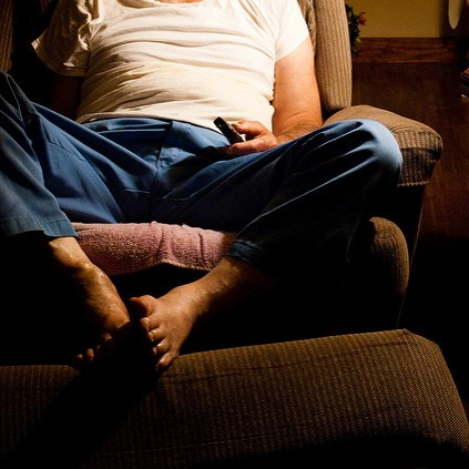 close up of man sitting in recliner - can't see his face - white tee and jeans barefoot